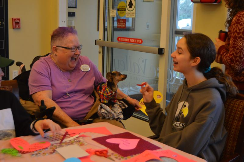 SPOTLIGHT PHOTO: NICOLE THILL - Helen Matthews, holding her dog Bear, and Anne Selby laugh together while making cards.