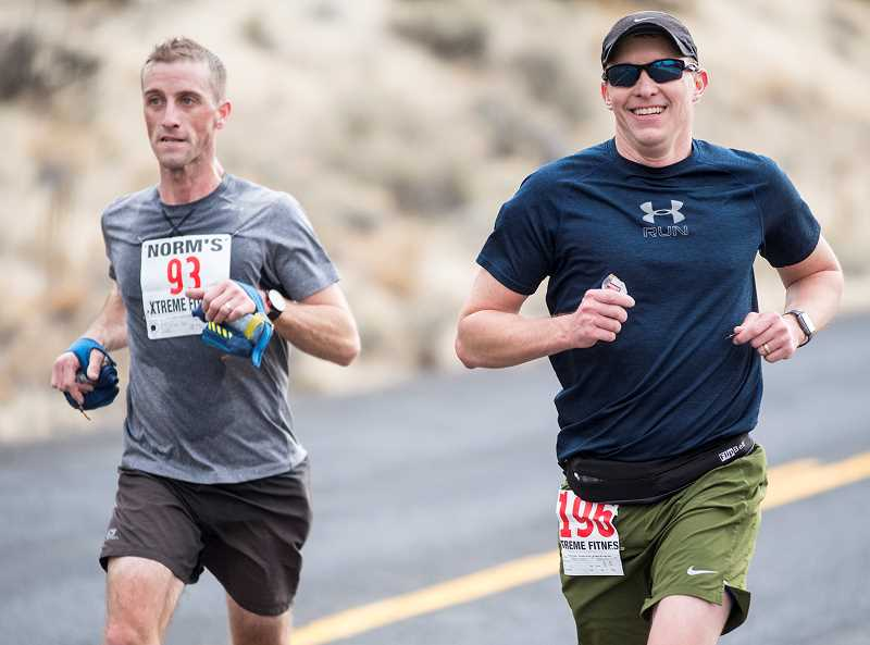 LON AUSTIN/CENTRAL OREGONIAN - Bend';s Peter Curran, left, and Prineville's Brandon Brasher run together as they near the halfway point of the 20-mile Xtreme Dam Run. Curran pulled away in the second half to win in a time of 2:10.23.