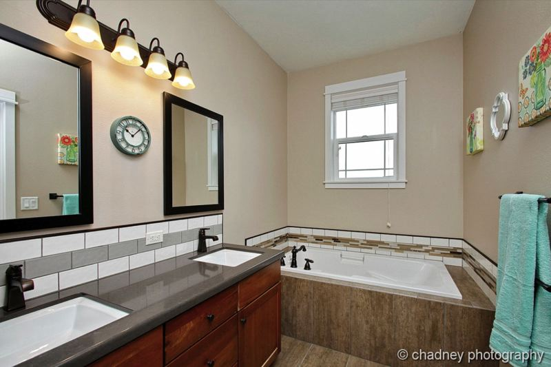 COURTESY CHADNEY PHOTOGRAPHY - A remodel of this bathroom included new mirrors and tasteful backsplash tile accents.