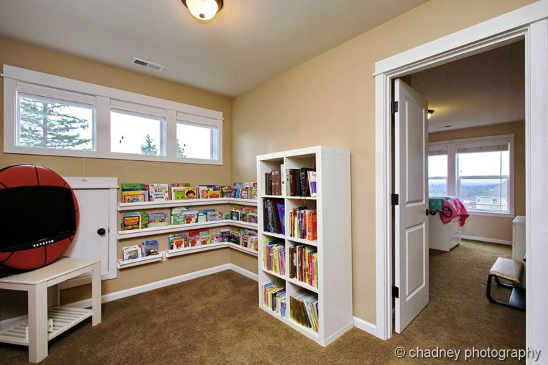 COURTESY CHADNEY PHOTOGRAPHY - A reading nook tastefully repurposes rain gutters to shelve books.