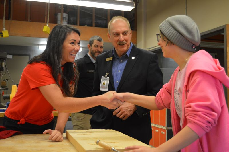 SPOTLIGHT PHOTO: NICOLE THILL - Kayleen McCabe, Tim Lawrence, and Kayla Jerome chat about a wood carving Jerome was completing in the high school wood shop on Friday afternoon.