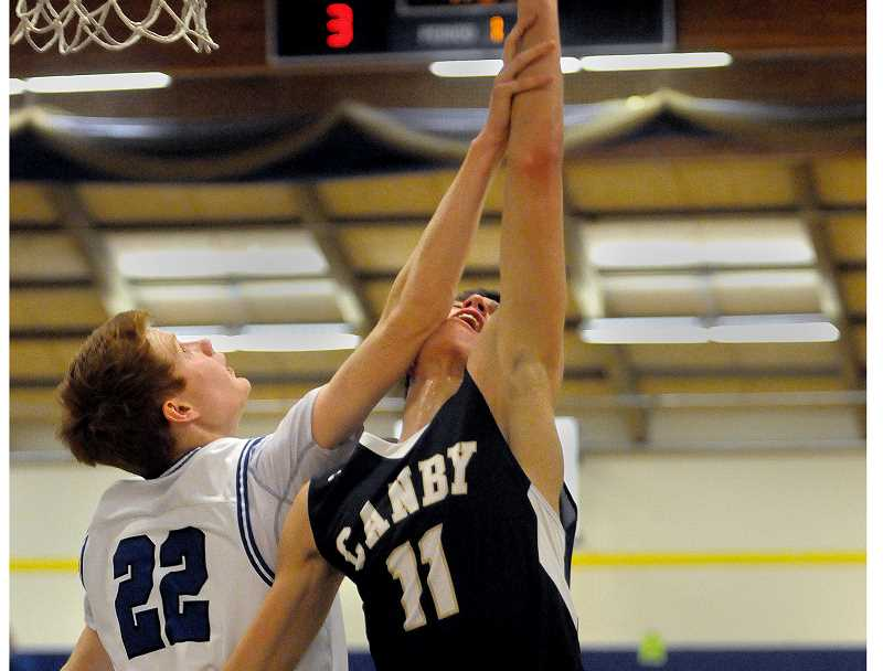 SETH GORDON - Canby's Rizdin Miller is fouled by Ben O'Loughin during the Cougar's 38-36 road loss at Newberg Friday night.