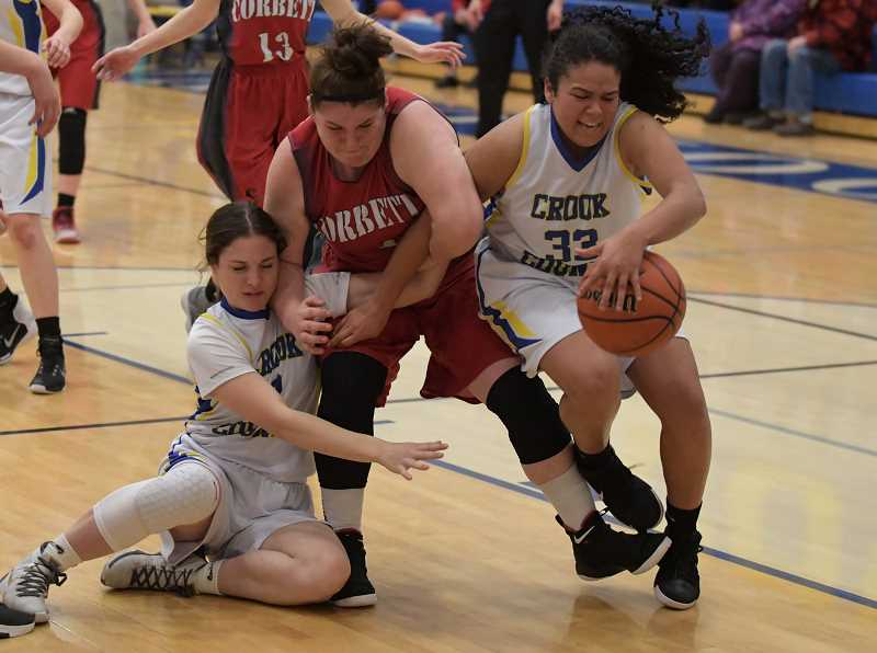 LON AUSTIN/CENTRAL OREGONIAN - Crook County's Kennedy Buckner, left, and Odessa Tramel-Green fight for a rebound with Corbett's Haley Swift. Swift was called for a foul on the play.