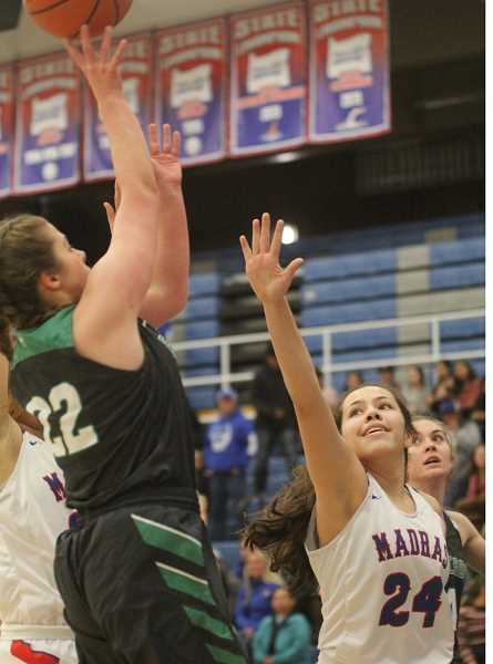 WILL DENNER/MADRAS PIONEER - Jayden Davis (right) contests an Estacada layup attempt in the first quarter.