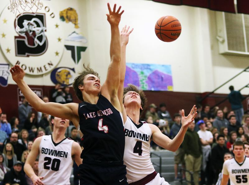 DAN BROOD - Lake Oswego junior Brandon Roberts (left) and Sherwood senior Nic Koronko battle for a rebound during Friday's game.