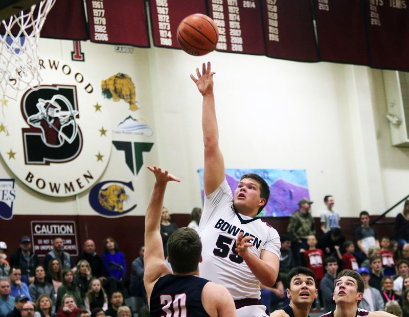 DAN BROOD - Sherwood senior Jace Sucher shoots over Lake Oswego senior Shawn Elliott during Friday's game.
