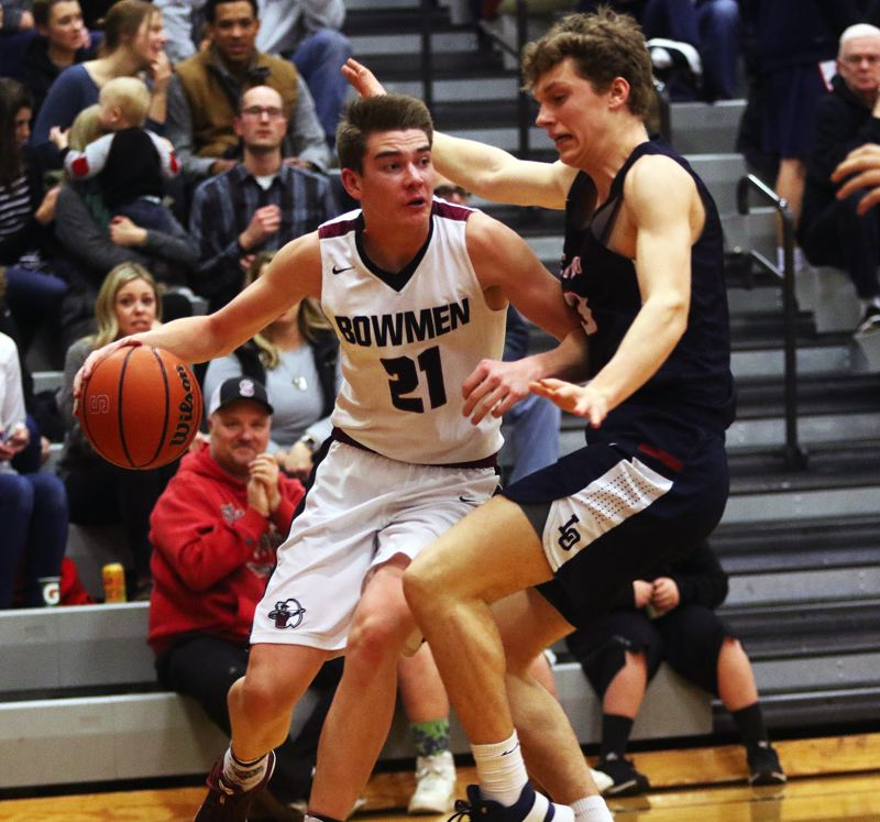 DAN BROOD - Sherwood junior Braden Thorn (21) tries to drive past Lake Oswego senior Brooks Boutwell during Friday's game.