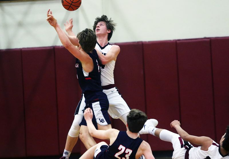 DAN BROOD - Lake Oswego junior Brandon Roberts and Sherwood senior Nic Koronko battle for a loose ball during Friday's Three Rivers League contest.
