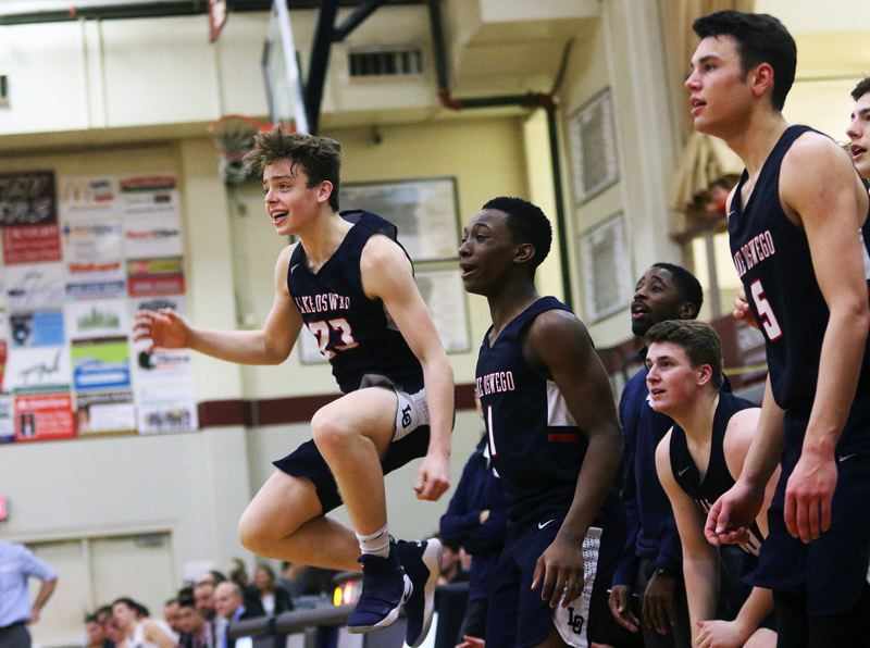 DAN BROOD - Lake Oswego junior Josh Angle (23) jumps into the air as he cheers on his teammates during the fourth quarter of Friday's game at Sherwood.