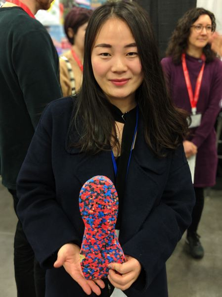 PAMPLIN MEDIA GROUP: JONATHAN HOUSE - A sales rep from Xingtalai Sports Products Co., shows off a foam sole. Knitted fabric based on Nikes Flyknit concept was everywhere, as were foam soles based on Adidas Boost.