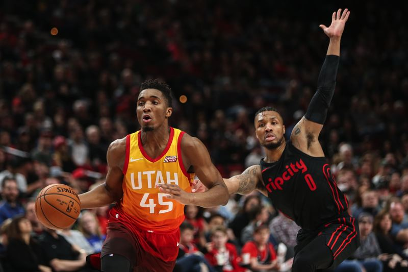 TRIBUNE PHOTO: DAVID BLAIR - Utah's Donovan Mitchell gets past Blazers guard Damian Lillard during Sunday night's Jazz victory at Moda Center.