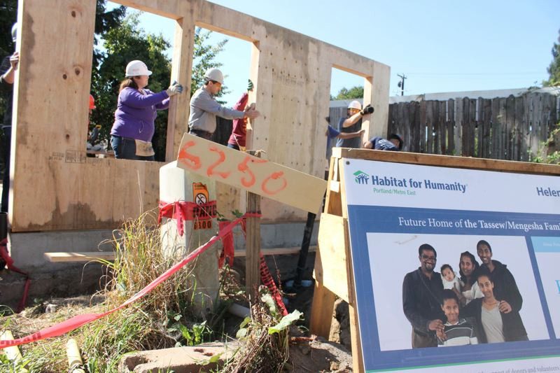 FILE - Habitat for Humanity volunteers from the Portland/Metro East chapter of the group raise a wall in Northeast Portland's Cully neighborhood in 2016.