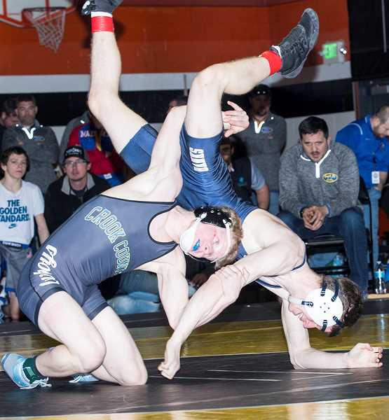 LON AUSTIN/CENTRAL OREGONIAN - Pacer Quire controls Jack Wick of Banks. Quire won by major decision to take the 120-pound championship. The Cowboys qualified 15 wrestlers for this weekend's state championships.