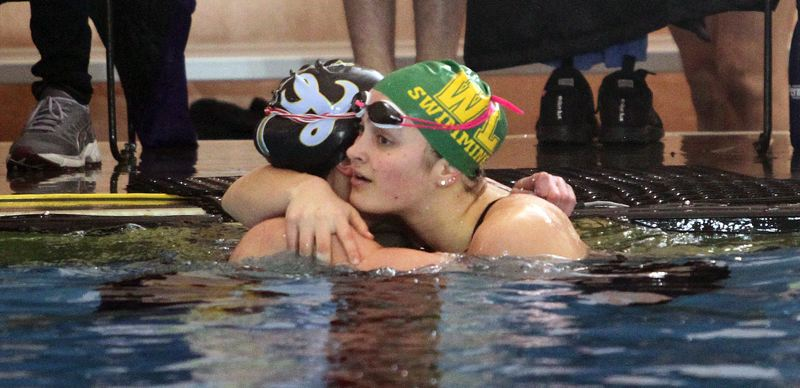 TIDINGS PHOTO: MILES VANCE - West Linn junior Katelyn Laderoute (right) hugs Lakeridge's Mara Newman after Newman and Laderoute went 1-2 in the 100-yard backstroke during the Three Rivers League district swim meet at Mt. Hood Community College Aquatic Center on Saturday.