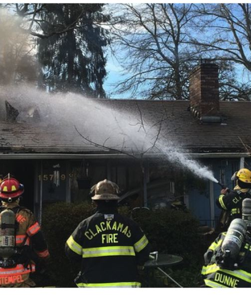 PHOTO COURTESY: CLACKAMAS FIRE - Clackamas firefighters extinguish a garage fire in Oak Grove on Feb. 10.