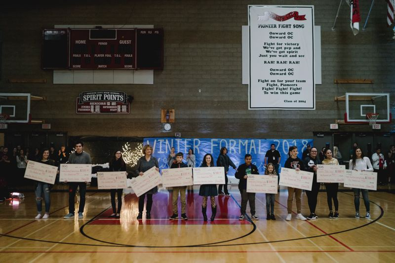 PHOTO COURTESY: MIKE LORD - Students or principals accept the checks from Oregon City High School during the Winter Formal assembly in which OCHS presented district elementary and middle schools with over $6,000 in money to help their students.
