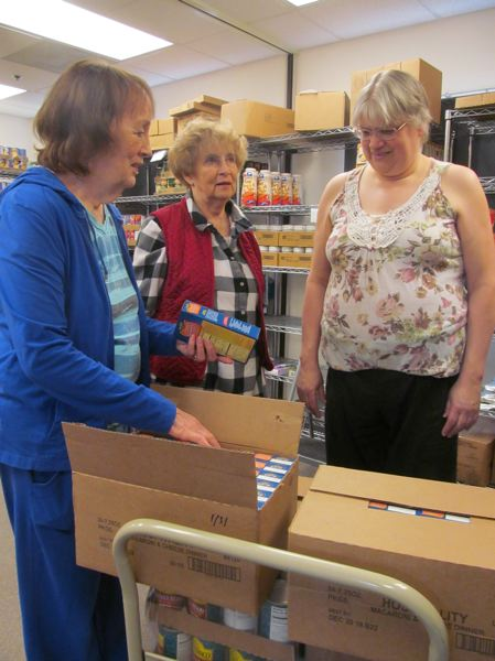 PHOTO BY ELLEN SPITALERI - From left, Carole King, Tonia Walker and Michelle Condit confer about where to put non-perishable items in the food pantry at the Oregon City Church of the Nazarene.