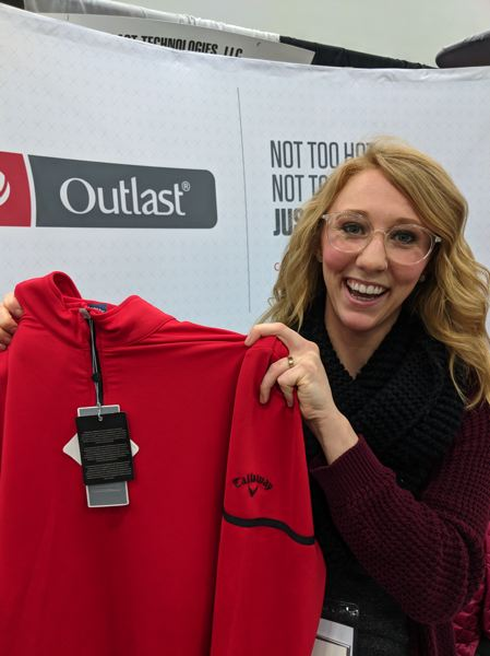 PAMPLIN MEDIA GROUP: JONATHAN HOUSE - Denver-based Outlast is a NASA patented material that feels extra cool to the touch adn is useful for sportswear. It is now owned by Coors Digital, which is owned by the beer company.  Here sales person Taylor Litzen shows off a golf shirt.