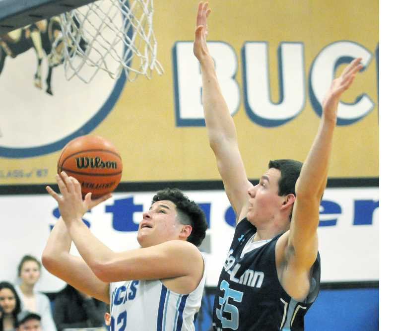 SETH GORDON - Sophomore post Alex Dela Cerda ducks past an East Linn Christian defender during St. Paul's 74-67 home win Friday night. The win clinched fifth place in the Tri-River Conference, the Bucks' highest in four years at the 2A level.