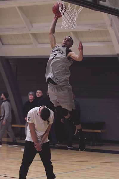 PHIL HAWKINS - MacLaren resident Dion leaps over a guest as he attempts a dunk after the ceremony to commemorate the new basketball court at MacLaren Youth Correctional Facility that was paid for by a $110,000 donation from the Salem Evangelical Church in 2017.