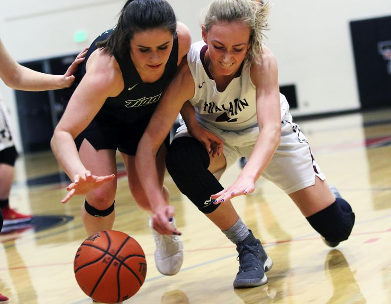 DAN BROOD - Tigard sophomore Kennedy Brown (left) and Tualatin junior Natali Denning dive for a loose ball during Tuesday's game.