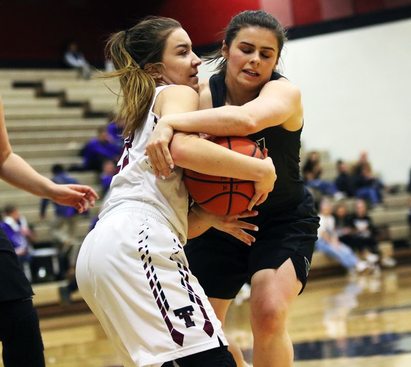 DAN BROOD - Tualatin senior Mikah Springer (left) and Tigard sophomore Kennedy Brown battle for the ball during Tuesday's game.
