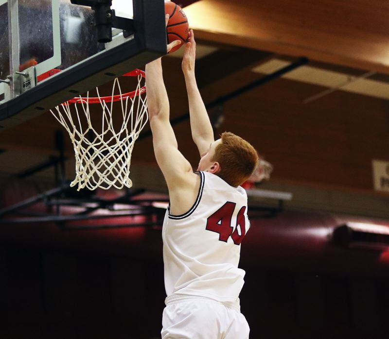 DAN BROOD - Tualatin junior Jack Rose goes up for a dunk, off a pass from senior Nathan Platter, during Tuesday's game with Tigard.