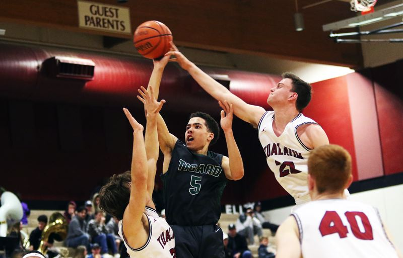 DAN BROOD - Tigard freshman Drew Carter (5) takes a jump shot while Tualatin senior Nathan Platter (right) goes for a block during Tuesday's game.