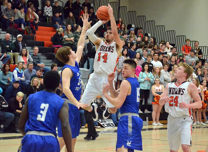 SPOTLIGHT PHOTO: JOHN BREWINGTON - Scappoose senior Chris Bendle hangs for a shot during his team's Tuesday home loss against Valley Catholic.