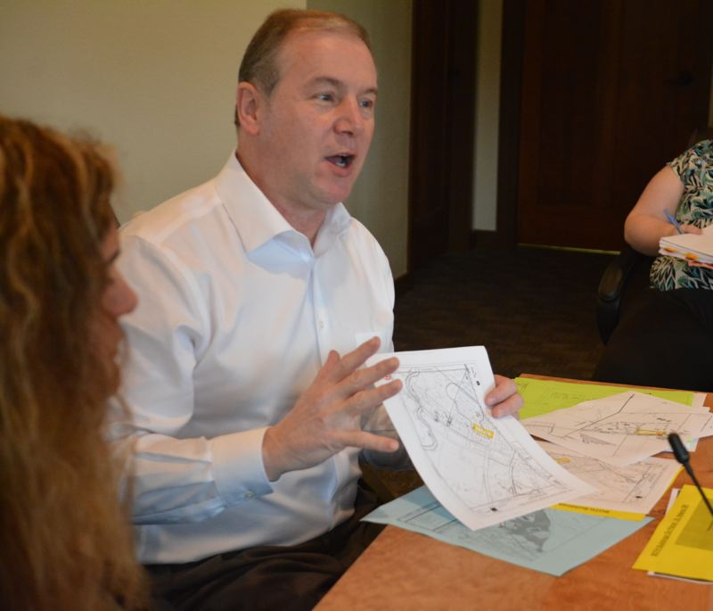SPOTLIGHT PHOTO: COURTNEY VAUGHN - Steven Fuhr holds up documents and maps supporting his companys desire to buy a nearly 1-acre lot from the Port of St. Helens. Fuhr works with Toucan Farms, a cannabis product company currently based in Washington.
