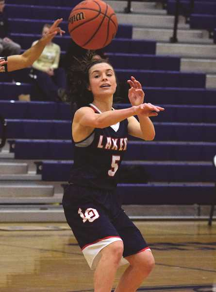 HERALD PHOTO: TANNER RUSS - Junior Katy Gilbert dishes the ball off to one of her teammates in Lake Oswego's Feb. 13 showdown with the Canby Cougars.