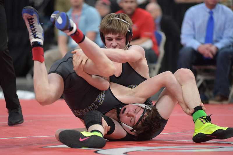 LON AUSTIN/CENTRAL OREGONIAN - Crook County High School teammates Hunter Mode, head down, and Steven Ware battle for control during the 106 pound finals at the state wrestling championships. Mode eventually earned a takedown and the win.