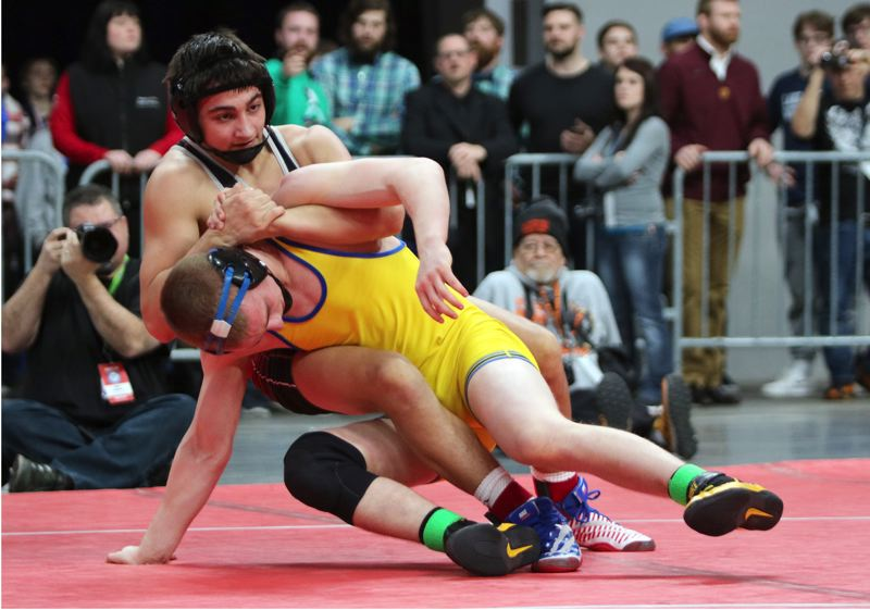 REVIEW/NEWS PHOTO: JIM BESEDA - Clackamas' Noah Wachsmuth (top) scored an 11-6 decision over Newberg's Taylen Reid to clinch the 145-pound title at Saturday's OSAA Class 6A wrestling championships.