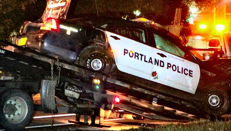 DAVID F. ASHTON - A wrecker pulled the smashed police patrol car up onto its flatbed, after it was hit by the fleeing driver of a stolen SUV.