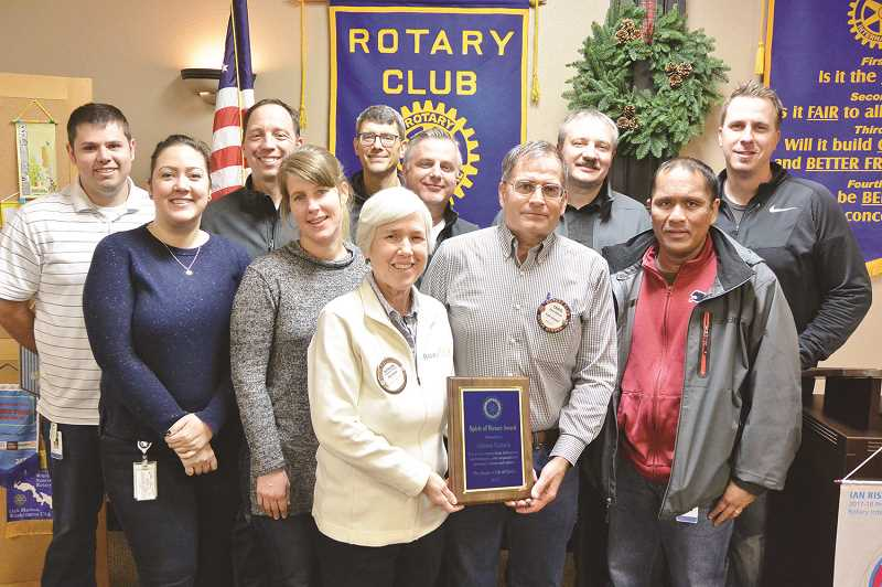 Pictured receiving the award are some members of one of their teams at Johnson Controls. President Kathleen Jordan presenting award (in front) to Rotarian Chris Nichols, manager at Johnson Controls.