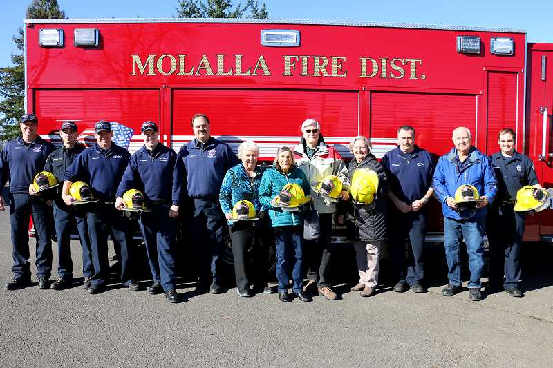 COURTESY PHOTO - Representatives from Molalla Communications and Molalla Fire show off the newly purchased helmets.