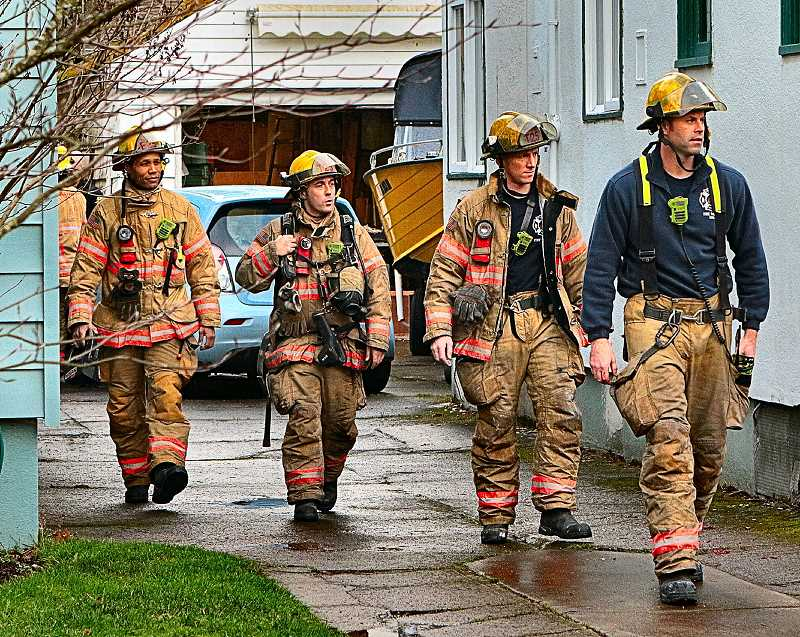 DAVID F. ASHTON - After making sure the fire was fully extinguished, crew members from PF&R Woodstock Station 25 gathered to return to their truck.