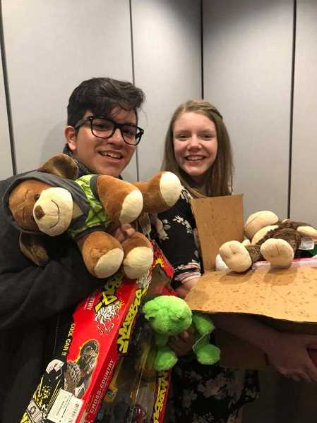 PHOTO COURTESY OF LAINIE MEAD - Dominic Robles (left) and Lainie Mead have their hands full with toys for a recent delivery at Doernbecher Children's Hospital.