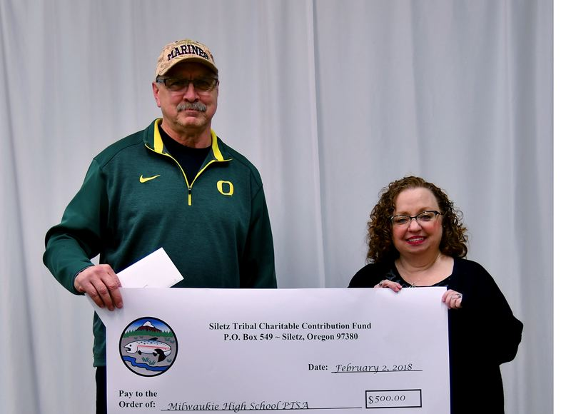 PHOTO COURTESY: ANDREA SUITTER - Milwaukie High School's Parent Teacher Student Association, represented by Cynthia Burmester, was presented with a check by Kurt Arden of the Siletz Tribal Charitable Contribution Fund.