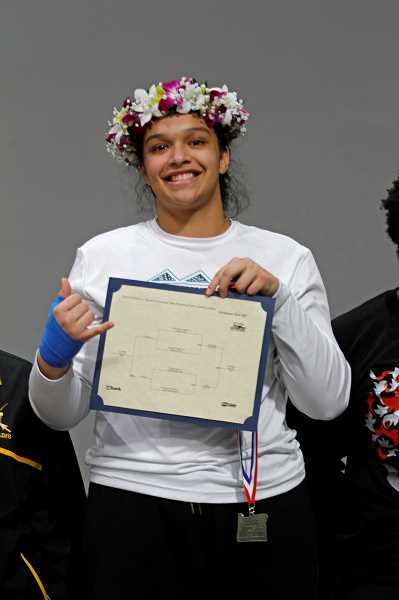 STAFF PHOTO: WADE EVANSON - Century's Mili-Nanea Nihipali accepts her medal for winning the 220-pound state championship at the 2018 State Wrestling Championships Feb. 17 at the Memorial Coliseum.
