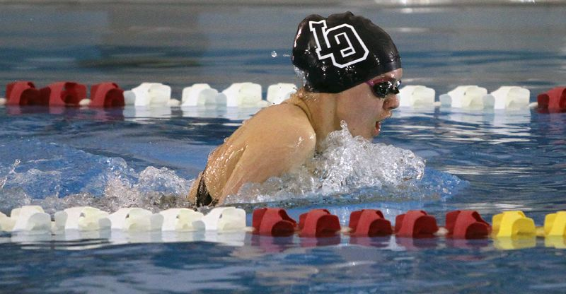 REVIEW PHOTO: MILES VANCE - Lake Oswego junior Grace Marshall breaks the surface of the water en route to a sixth-place finish in the 100-yard breaststroke at the Class 6A state swim meet at Mt. Hood Community College Aquatic Center on Saturday.