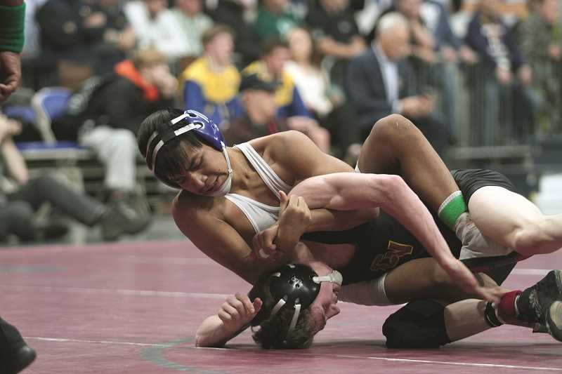 PHIL HAWKINS - Woodburn's Wesley Vasquez works from the top against Crescent Valley's Drew Roberts in the championship match of the 5A 113-pound state wrestling bracket.