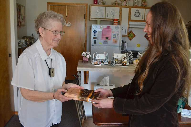 PAMPLIN MEDIA PHOTO: BRITTANY ALLEN - Leslie Pearson (right) hands a book to Eleanor Spink (left) in her Whispering Pines apartment. Spink participates in Estacadas library-to-your-door program, which connects those who are unable to visit the library with books.