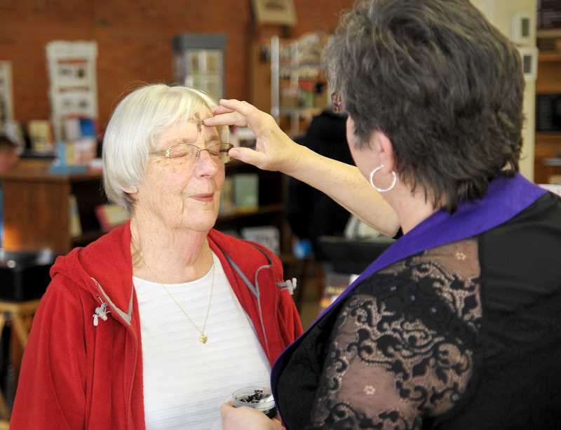 SETH GORDON - Newberg First United Methodist Pastor Cathy Davis uses palm ashes to mark a cross on the forehead of Esther Springer last week at Chapters Books and Coffee. Davis and Joyful Servant Lutheran Pastor Kim Hester provided 'Ashes to Go' to celebrate Ash Wednesday and the beginning of Lent.
