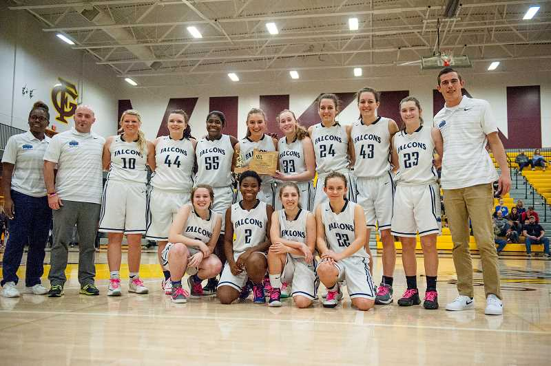 COURTESY PHOTO - The Faith Bible Falcons girls basketball team poses for a photo with their hardware following their NWL Championship Game victory Feb. 17 at Forest Grove High School.