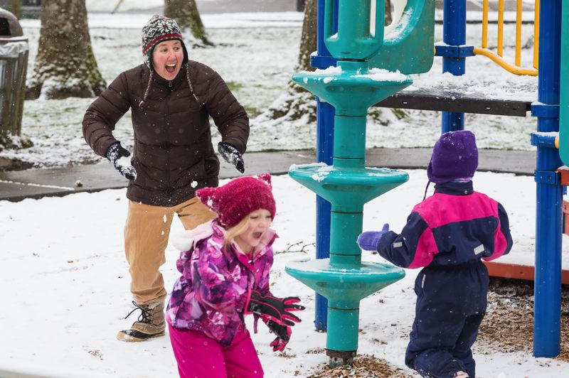 STAFF PHOTO: CHRISTOPHER OERTELL - Stacey Halpern has a snowball fight with her daughter Carina, 6, and her friend Maple Miller, 6, at Rogers Park in Forest Grove on Tuesday.