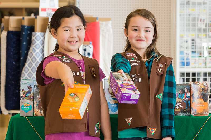 STAFF PHOTO: CHRISTOPHER OERTELL - Hillsboro Girl Scouts Jasmine Cummings, 7, and Abrielle St. Claire, 9, sell boxes of Girl Scout cookies at the Sunset Esplanade. The girls plan to sell thousands of cookies this year.