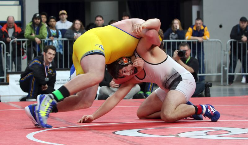 REVIEW/NEWS PHOTO: JIM BESEDA - Oregon City's Lane Marshall gave up 35-40 pounds to 270-pound Tristan Osborn of Newberg in Saturday's heavyweight final at the OSAA Class 6A wrestling championships.