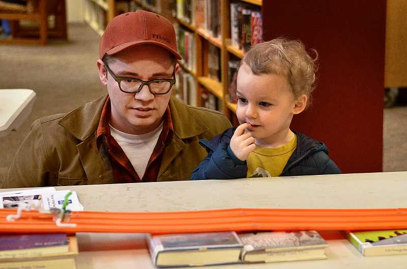 REVIEW PHOTO: VERN UYETAKE - Matt and 3-year-old Henrick Reed test out their Arctic Crawler on a race track during a hands-on Lake Oswego Reads event at the library.