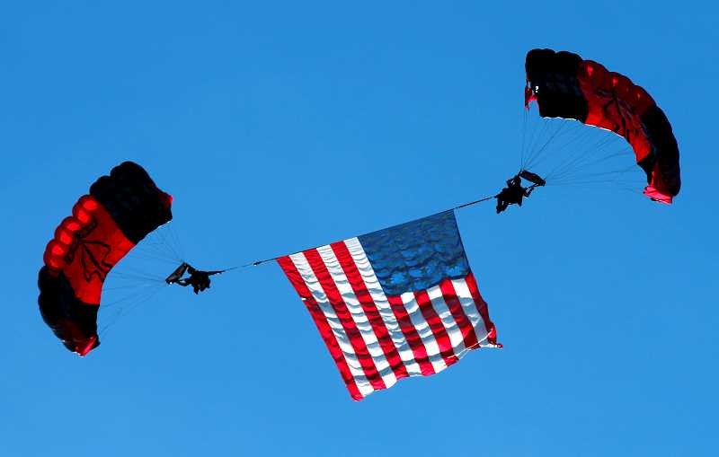SUBMITTED PHOTO - Two volunteers, part of the U.S. Army Special Operations Command Parachute Demonstration Team, the Black Daggers, carry a large U.S. flag between them. The Black Daggers will be at the 2018 Airshow of the Cascades Aug. 24-25, for the first time.
